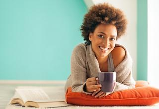 Woman holding coffee smiling | Dentist Toronto ON