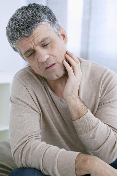 man holding his jaw from pain
