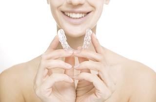 Woman holding clear braces | Invisalign Toronto ON