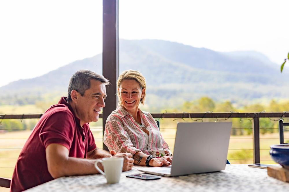 older man and woman sitting on porch working on laptop