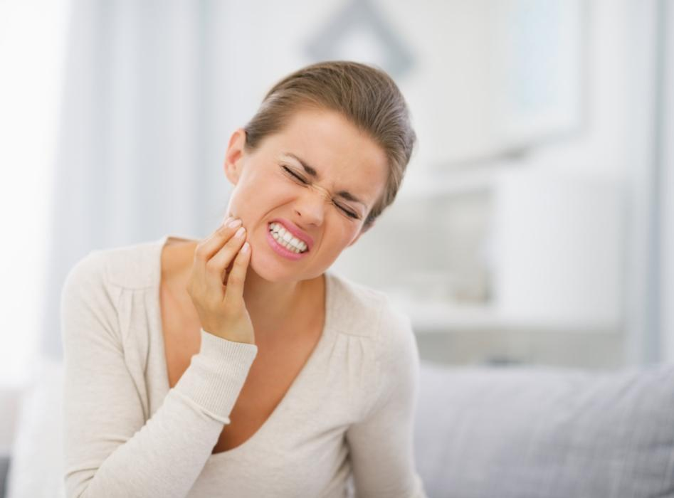 Woman holding jaw from pain | Toronto Lakeshore Dental