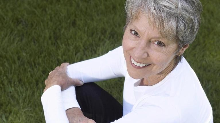 Older woman smiling and sitting in the grass