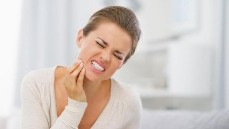 Woman holding jaw from pain | Toronto Dentist