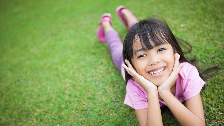 Young girl lying on grass and smiling
