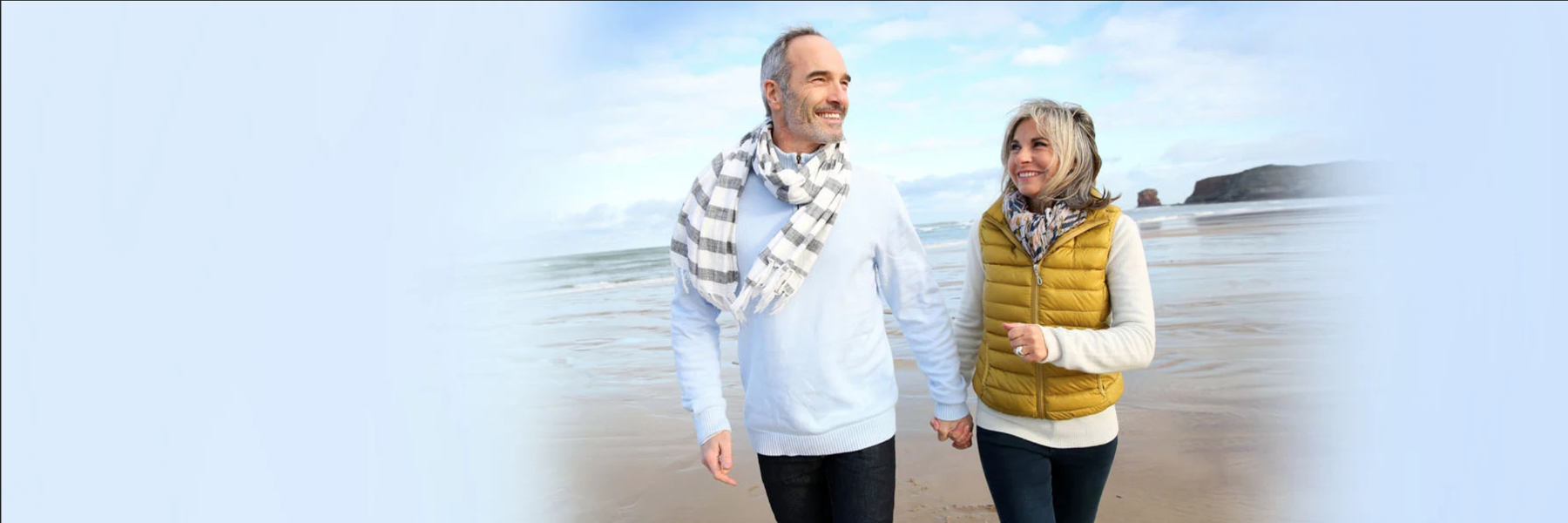 Older couple walking on the beach | Toronto Lakeshore Dental